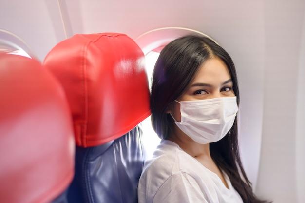 機内で保護マスクを着用した旅行中の女性