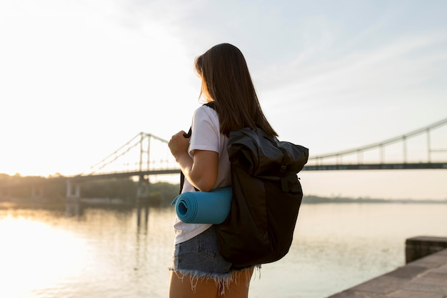Traveling woman with backpack admiring the view of river