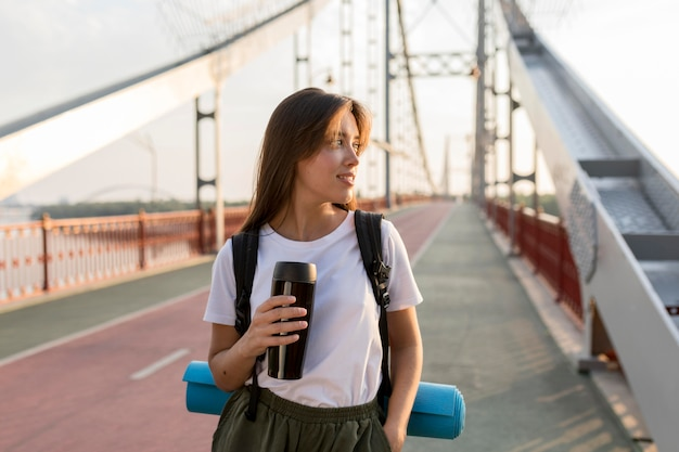 Traveling woman with backpack posing on bridge while holding thermos
