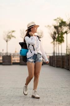バックパックを運ぶ帽子を持つ旅行女性