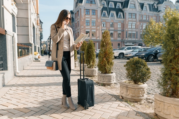 Traveling young woman with mobile phone and suitcase