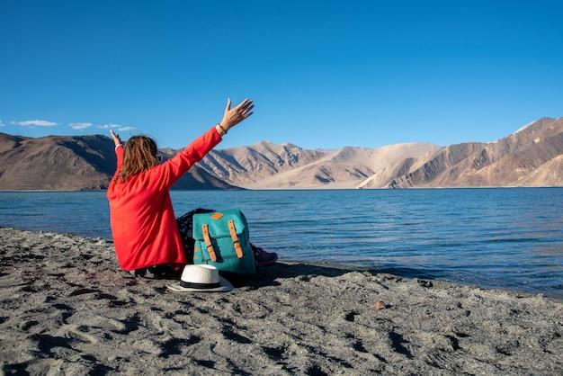 Traveller backpack woman raised hands on the beach of pangong lake or pangong tso, ladakh, jammu and kashmir, india.