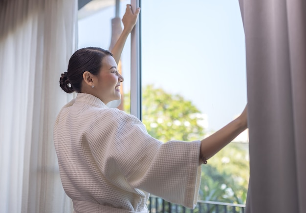 여행자 아름다운 아시아 여자는 호텔 방의 문 근처에 머물러 거기를보고 미소