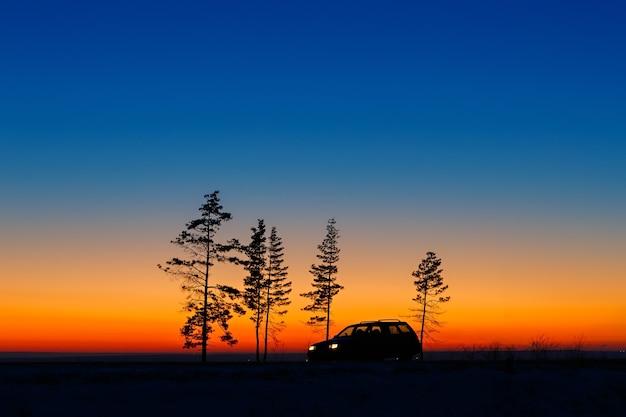 Автомобиль путешественника на фоне яркого заката.