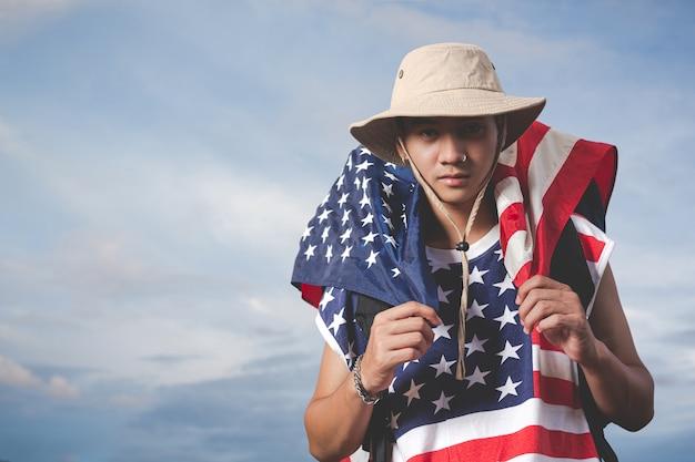 空の景色の前に旗を持っている旅行者