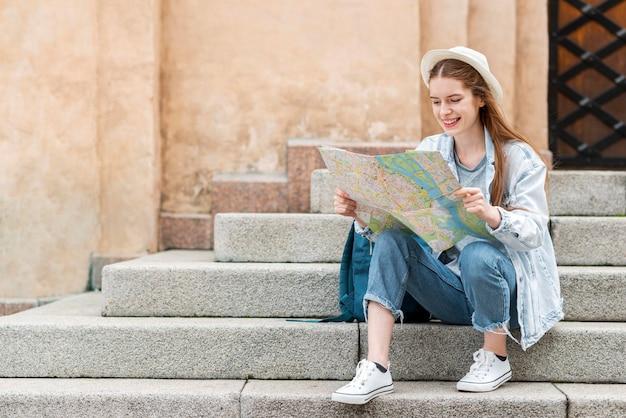 地図を押しながら階段の正面に座っている旅行者