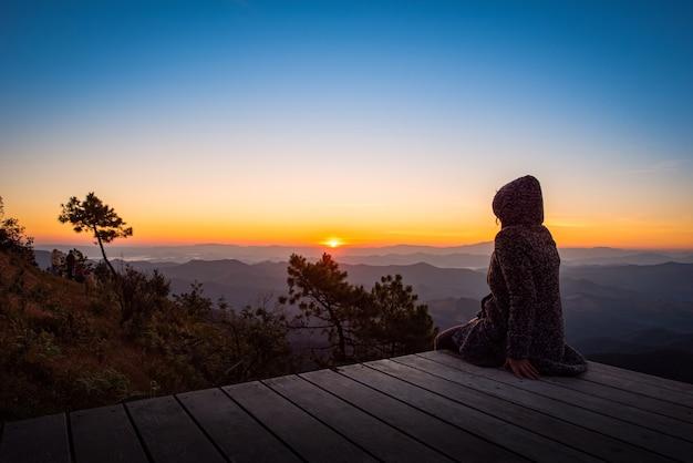 Путешественник смотрит на восход солнца на вершине горы
