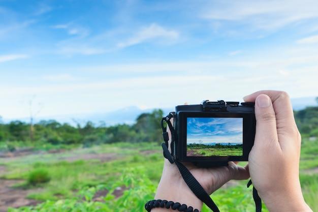 Путешественник делает фото с помощью беззеркальной камеры в руке, путешествует блоггер.