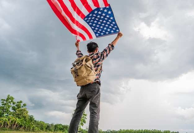 Человек путешественник, холдинг американский флаг сша открытый с грозой облачно фон.