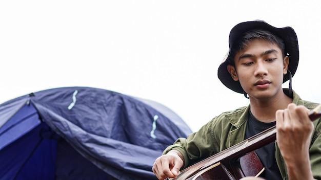 Путешественник играет на гитаре в лагере