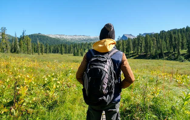 Traveller man with backpack looking to mountains. back view.