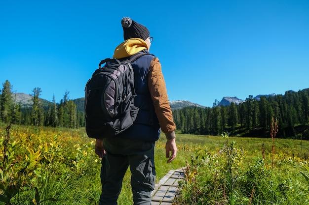 산을 찾고 배낭 여행자 남자입니다. 뒷모습.