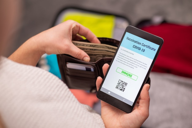 旅行の準備をし、現金をチェックし、予防接種文書の電子コピーを持って電話を見る旅行者