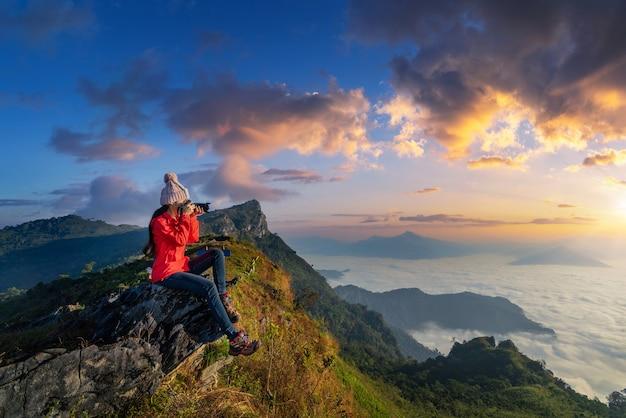 바위에 앉아 카메라를 들고있는 여행자는 태국 치앙 라이의 도이 파몬 산에서 사진을 찍습니다.