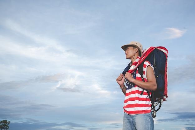 空の景色の前に立っている旅行者