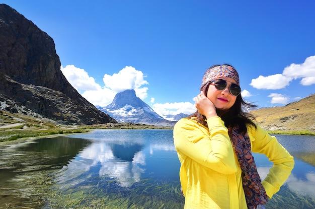 Traveller standing near the alpine lake of riffelhorn in front of mountain matterhorn peak, zermatt, switzerland.
