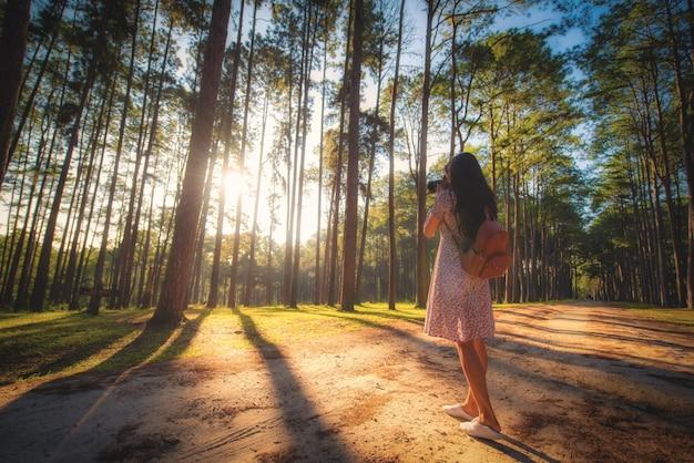 Путешественник сфотографируется на восходе солнца на лесоводческой исследовательской станции боа кео