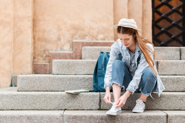 Traveller tying her shoelaces on the stairs