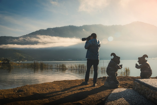 Traveller using a dslr camera take photo of pura ulun danu bratan at sunrise in bali, indo