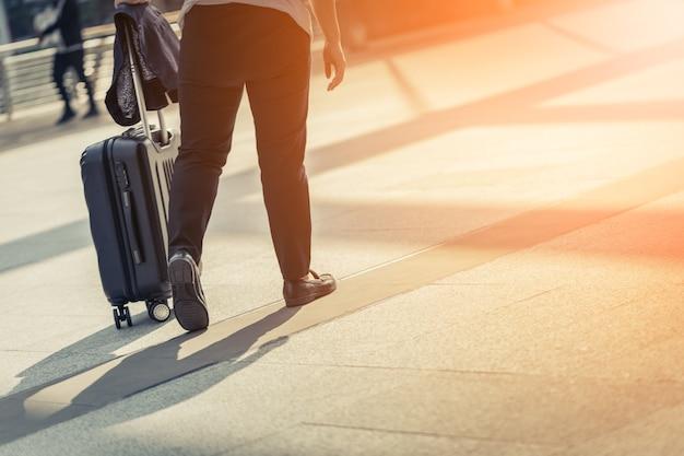 Прогулка по улицам с чемоданом с концепцией путешествия на закате солнца