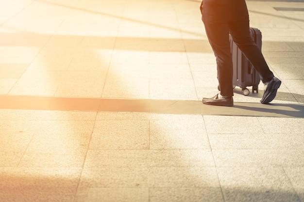 Прогулка по улице на улице с чемоданом с закатом света