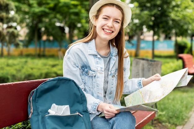 医療用マスクと地図を身に着けている旅行者