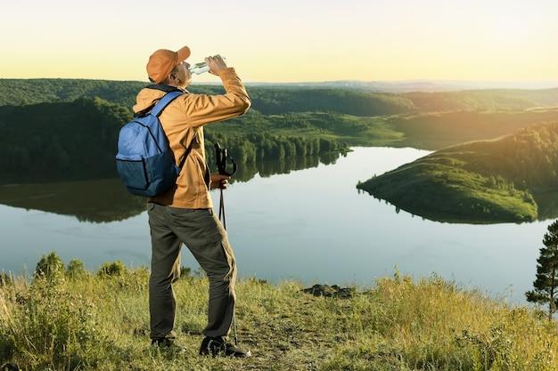 日没時の秋の山でペットボトルから水を飲むバックパックを持つ旅行者。アクティブな健康的なライフスタイルの冒険の旅の休暇