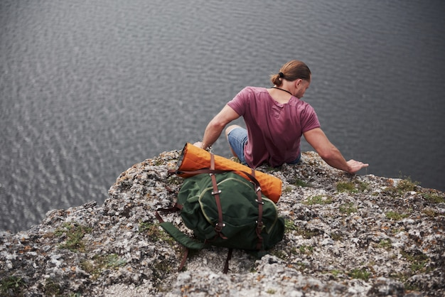 Traveller with backpack sitting on top of mountain enjoying view above the water surface. freedom and active lifestyle concept