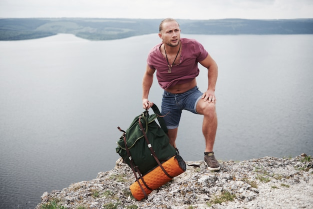 Traveller with backpack sitting on top of mountain enjoying view above the water surface. traveling along mountains and coast, freedom and active lifestyle concept
