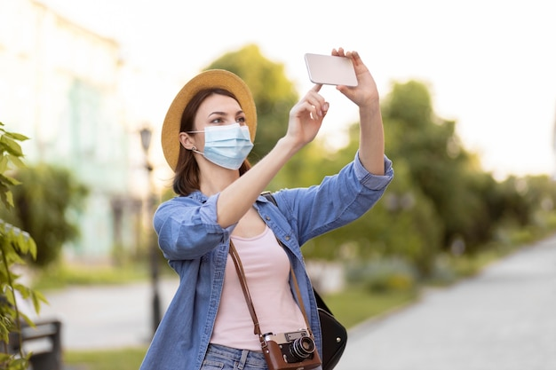 フェイスマスクと帽子の写真を撮る旅行者
