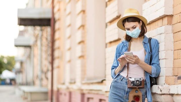携帯電話を閲覧する帽子とフェイスマスクを持つ旅行者
