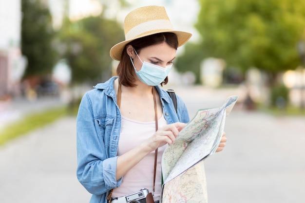 マップをチェックする帽子とフェイスマスクを持つ旅行者