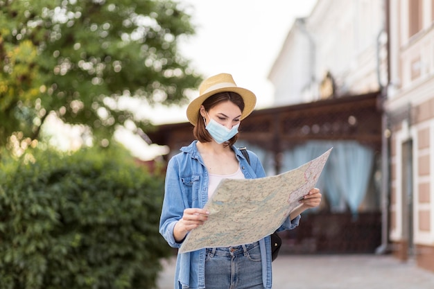 Traveller with hat and medical mask checking map