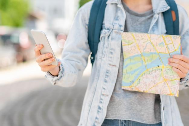 地図と携帯電話の正面図を持つ旅行者