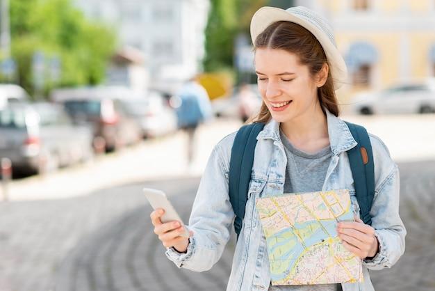地図と携帯電話のミディアムショットを持つ旅行者