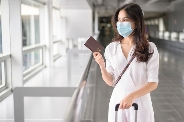 A traveller woman is wearing protective mask in international airport, travel under covid-19 pandemic, safety travels, social distancing protocol, new normal travel concept .