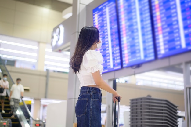 A traveller woman is wearing protective mask in international airport, travel under covid-19 pandemic, safety travels, social distancing protocol