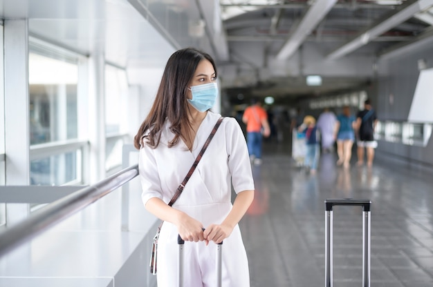 A traveller woman is wearing protective mask in international airport, travel under covid-19 pandemic,