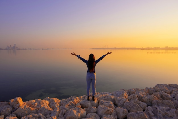 Traveller woman wearing jeans standing on the rocks shore open armds over sea and colorful sunrise sky background, bahrain.