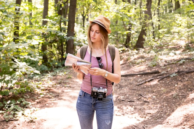 Traveller in woods looking at map