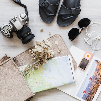 Travelling accessories with map and flower in the handbag over the desk