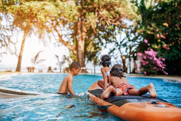 태국 여행 및 레크리에이션. 수영복을 입은 세 명의 청소년이 보트를 타고 수영장에서 함께 놀고 즐거운 시간을 보내고 있습니다.