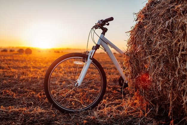 自転車で旅行する。秋のフィールドの背景に干し草の山が残したマウンテンバイク。スポーツライフスタイル
