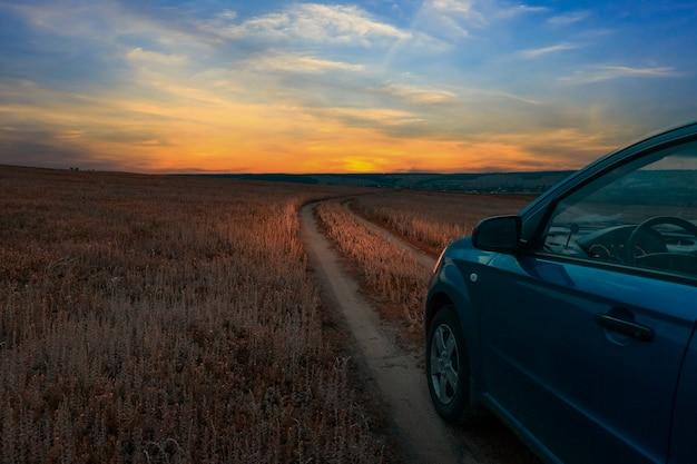 Путешествие на машине. проселочная полевая дорога на закате. сельский пейзаж.
