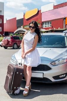 旅行の概念、スーツケースと車を持つ女性
