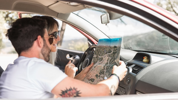 Travelling couple sitting in the car looking at map
