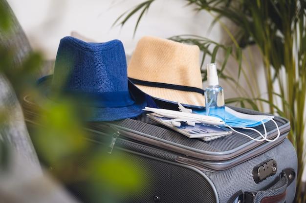 コロナウイルスの流行中の旅行。パスポートと手指消毒剤付きの保護フェイスマスク。コロナウイルスと旅行のコンセプト。