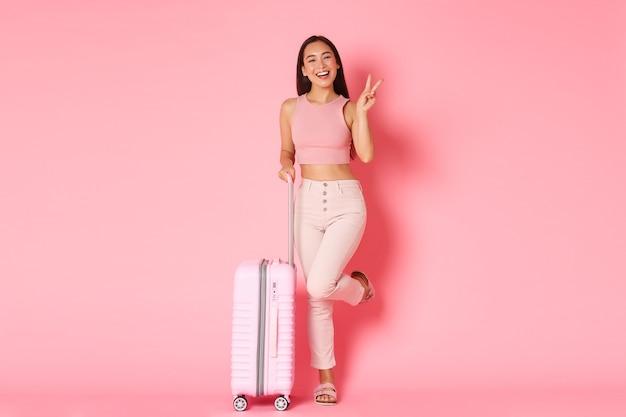 旅行、休日、休暇のコンセプト。夏服の陽気なアジアの女の子は海外旅行のためのバッグを詰めました