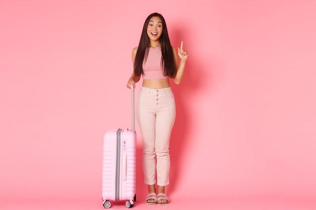 Путешествие, отпуск и концепция отпуска в полном объеме удивленной мечтательной азиатской девушки-туриста, име ...
