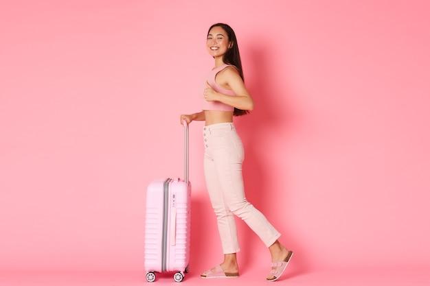 旅行、休日、休暇のコンセプト。夏服で魅力的なアジアの女の子の観光客の笑顔